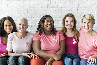 Five women of different ethnicities and ages smiling at the camera while all wearing pink and wearing pink ribbons to represent breast cancer