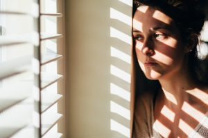Woman looking outside, with the blinds casting shadows on her face and body
