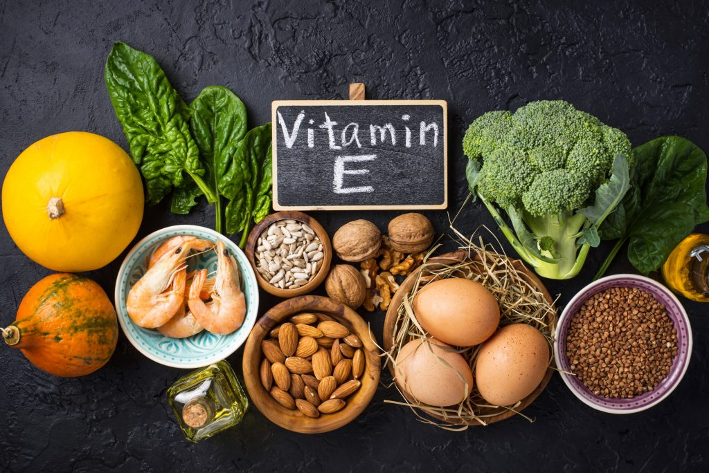 "Chalkboard with ""vitamin E"" written on it, surrounded by foods such as squash, shrimp, nuts, eggs, seeds, oil, broccoli, and more."