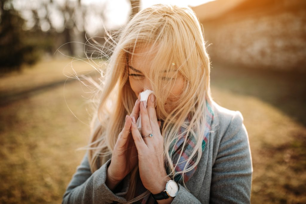 Woman with blonde hair blowing her nose