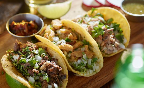 Three Tex-mex taco with meat, vegetables, salsa, and garnishes