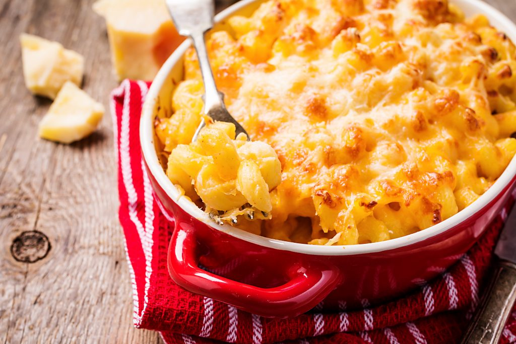 Red casserole dish with mac and cheese, a soul food classic