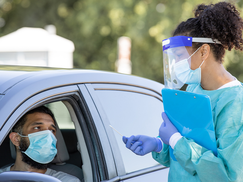 Man with medical face mask sitting in a car while getting ready to receive a COVID-19 test from a medical professional in blue scrubs and a face shield