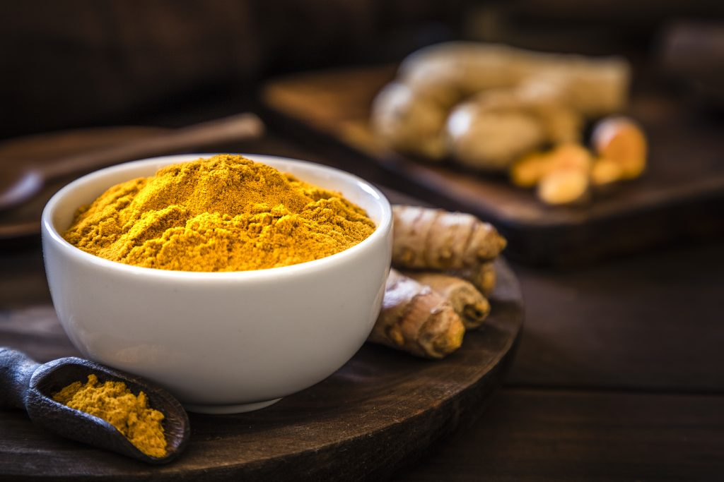 Raw and ground turmeric presented on a wood board and a white bowl
