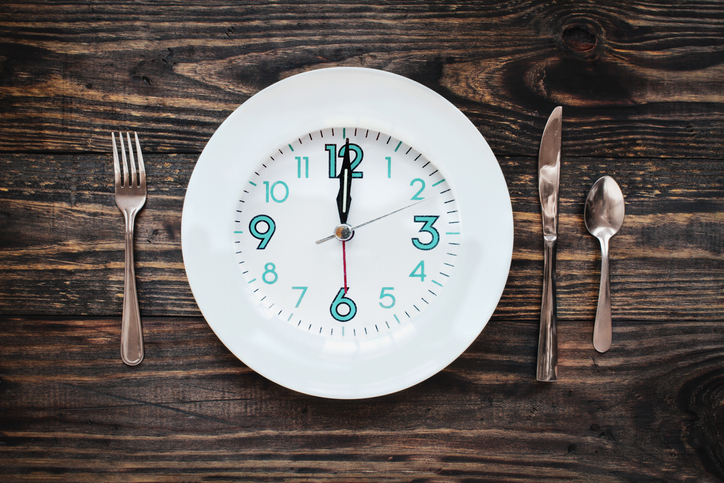 A plate with a clock on it and table setting with silverware