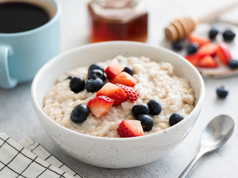 Oatmeal porridge with berries, honey and cup of coffee, at a table setting with coffee and other breakfast foods