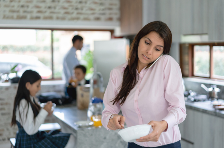 Woman in pink blouse on the phone and eating, while two children and a man eat breakfast in their kitchen