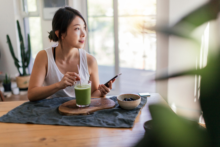 A woman enjoying a green smoothie and a bowl of breakfast food