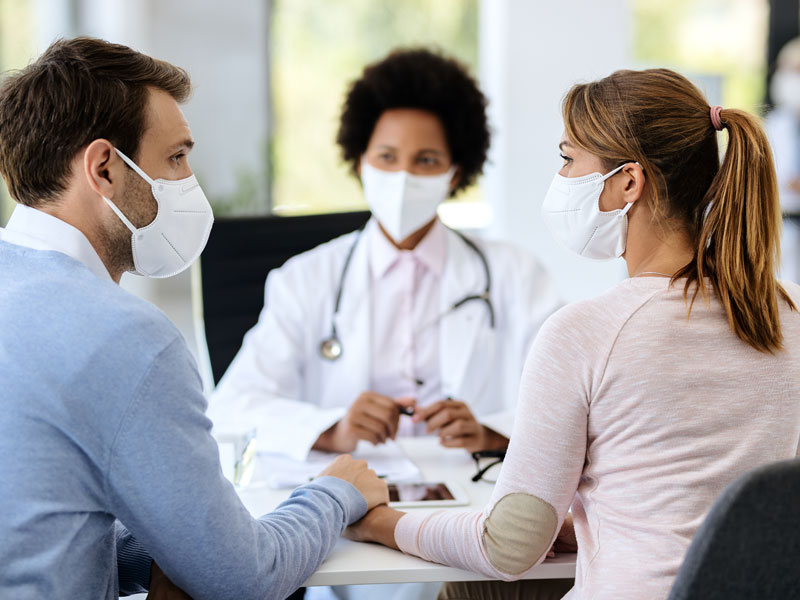 A man and a woman talking with a medical professional while wearing face masks, used to explain infertility issues