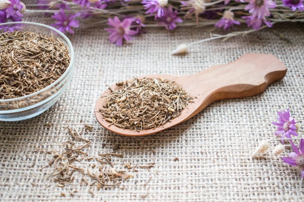 Valerian root in a bowl and on a wooden spoon, which can be used for sleep aids