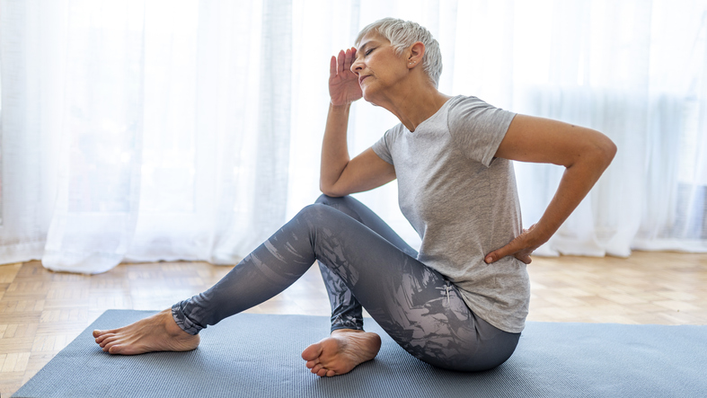 An older woman sitting on a yoga mat, holding her head and lower back
