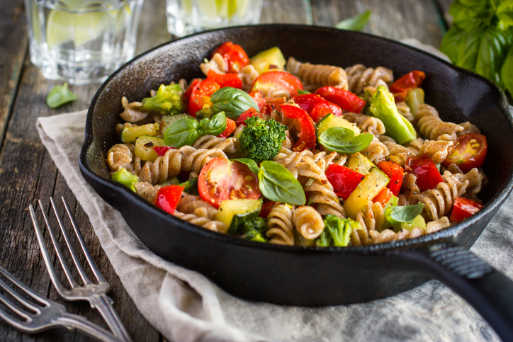 Whole wheat pasta with spinach, tomatoes, and vegetables in a cast iron pan