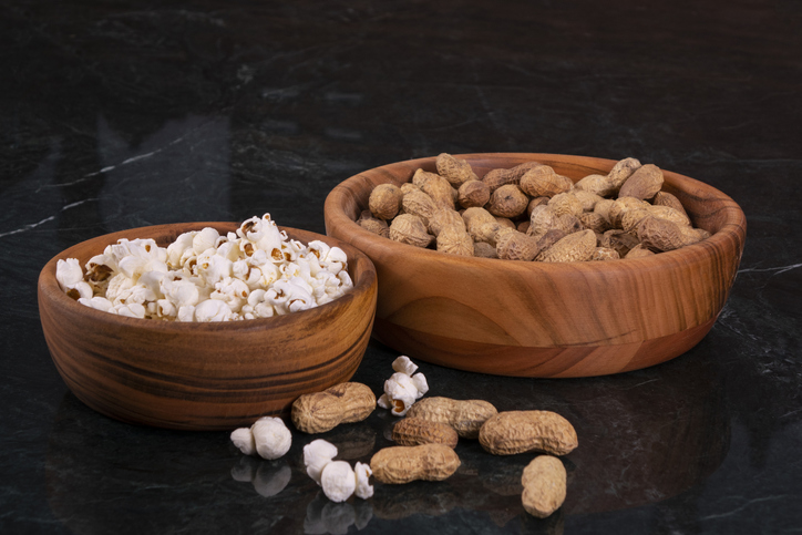 Peanuts and popcorn in wooden bowls