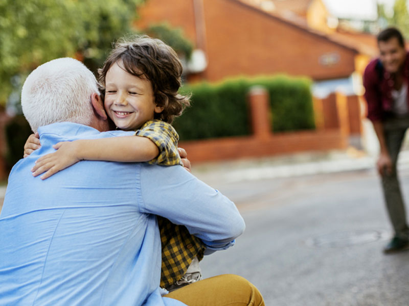 An older man and child hugging, used to explain what actions are safe after getting vaccinated for COVID-19