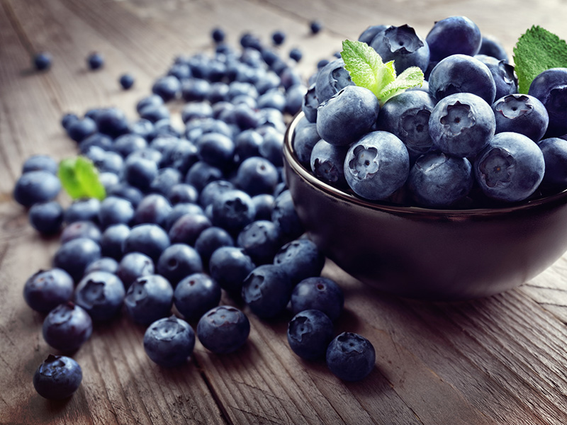 Blueberry antioxidant organic superfood in a bowl on a rustic table to help explain foods that reduce inflammation