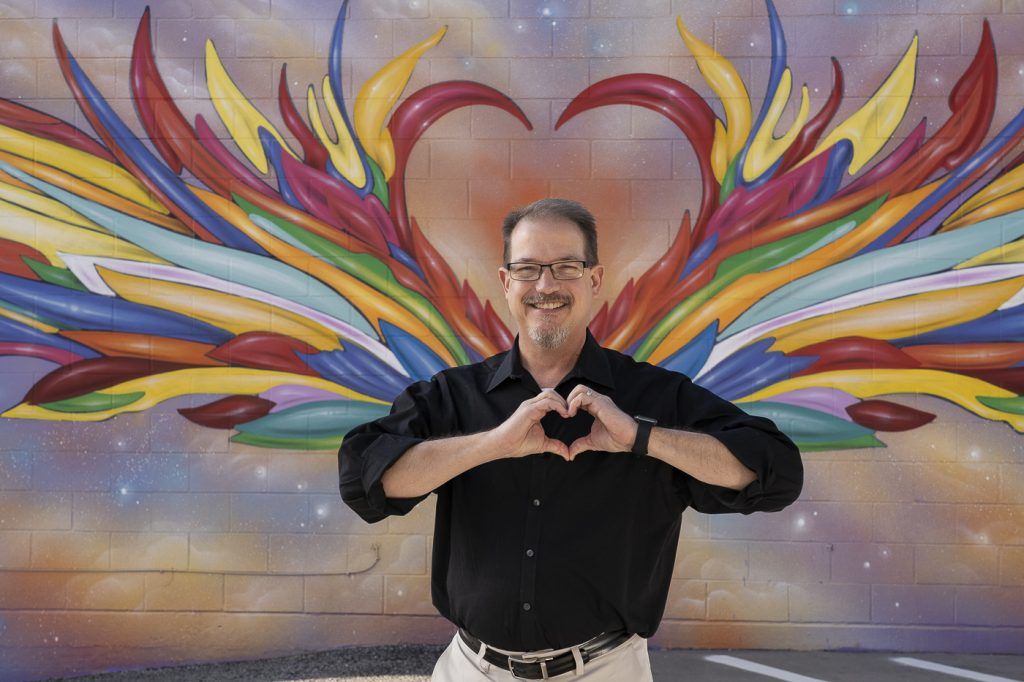 Chuck Roe standing in front of a heart mural in downtown Mansfield, Texas
