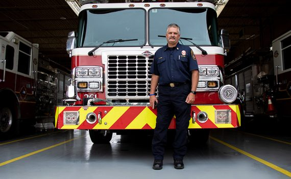 DeSoto firefighter Craig Kirk standing in front of a fire truck