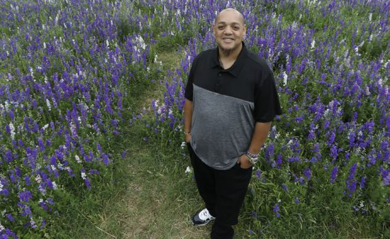 Daniel Lauriano smiling at the camera and standing in a field of purple flowers,photographed after his widow maker heart attack