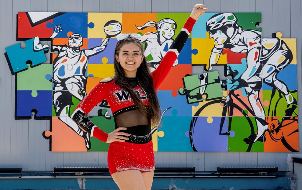 Chloe Galvez dressed in her cheerleading uniform in front of a mural with puzzle pieces and bright colors