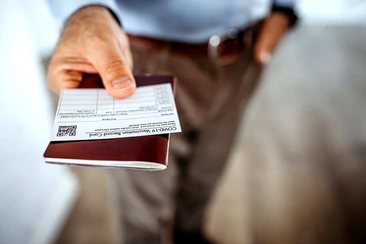A person holding their COVID-19 vaccination card along with other identifying paperwork