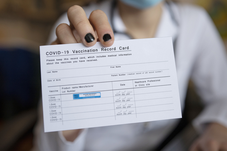 Someone holding their COVID-19 vaccination card
