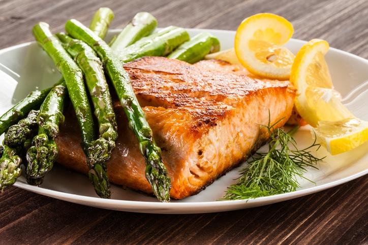 Prepared dinner of salmon, asparagus, dill and lemon on a dinner plate