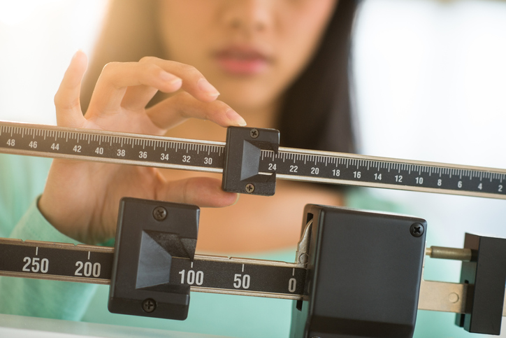 Woman sliding a scale to measure her weight