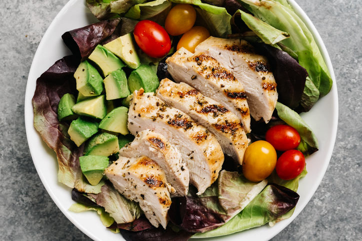 A photo of a salad with grilled chicken, avocado, lettuce, and baby tomatoes