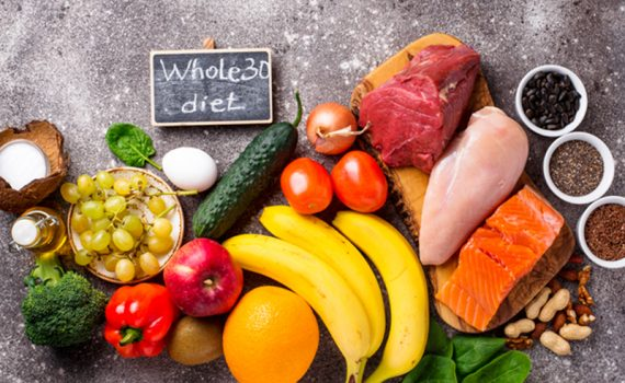 """An array of fresh foods and produce with a chalk sign that says """"Whole30 diet"""""""