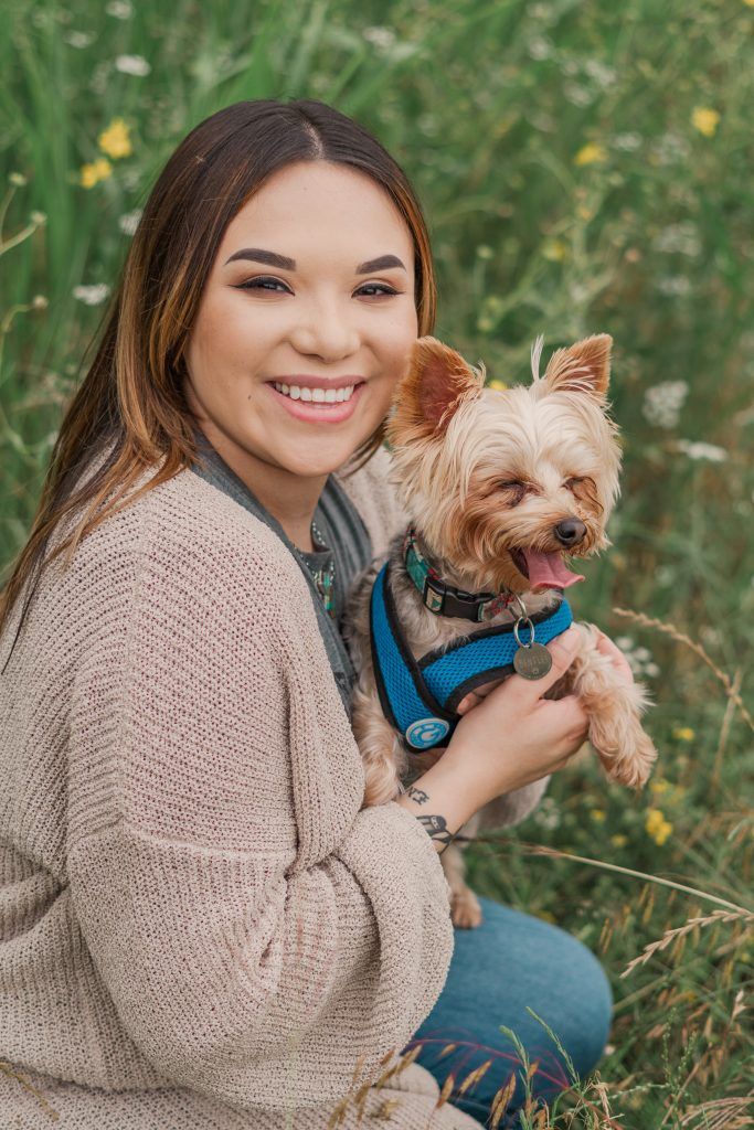 Amy Jackson photographed with her Yorkie in a field while wearing a pink cardigan, gray shirt and jeans.
