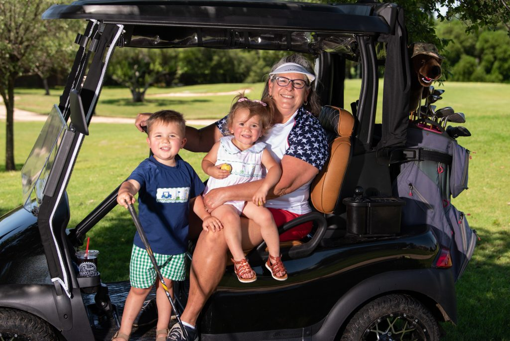 Mimi Leasor on a golf cart with two of her grandchildren