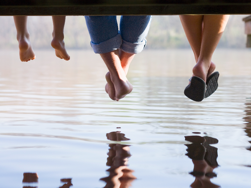 Three sets of feet dangling over water, used to explain summer foot care tips