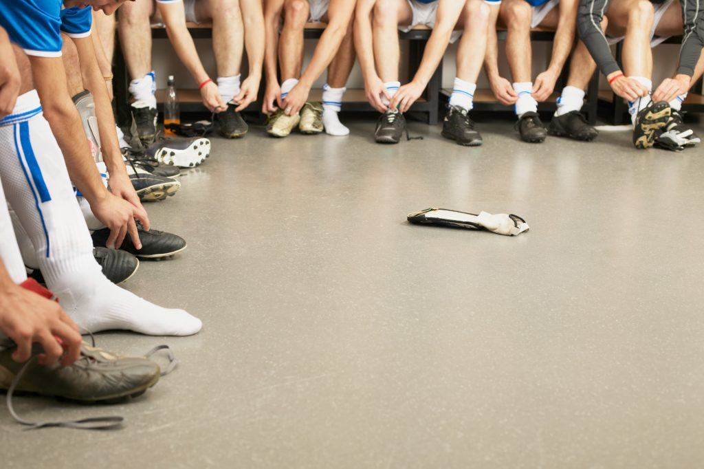 A group of people in a locker room lacing up athletic shoes and putting on socks