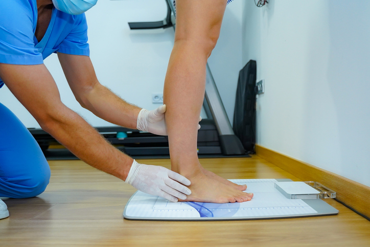 A medical professional assisting someone standing and supporting their feet