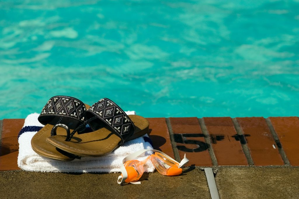 A set of sandals, goggles, and a towel sitting pool-side