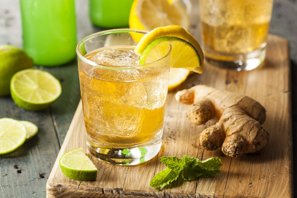 Glass of liquor in a glass with lime, lemon, mint, and ginger