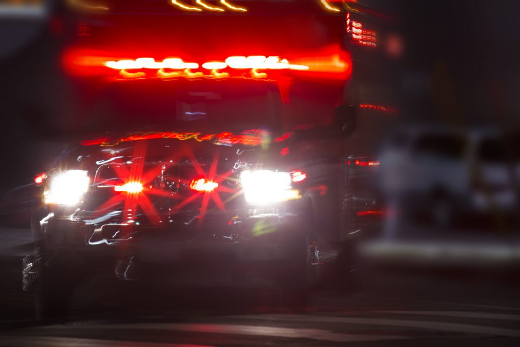 Ambulance driving at night whose red lights are on