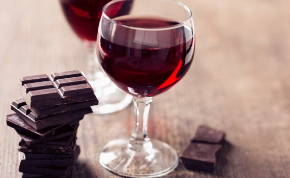 Red wine in glasses with pieces of chocolate bars, used to explain the sirtfood diet