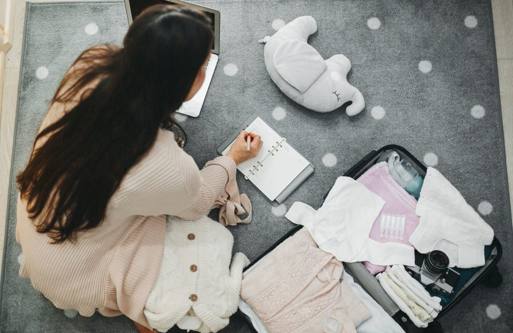 A woman surrounded by new baby clothes and toys, writing notes and a birth plan in a notebook