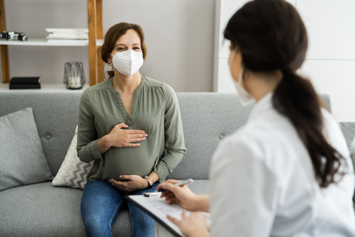 A pregnant woman holding her belly and speaking to a medical professional, possibly about a birth plan or labor details