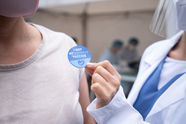"""A medical professional holding a button that says """"I got my COVID-19 vaccine"""""""