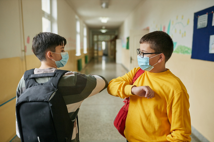 Two kids in masks bumping elbow when they are back to school
