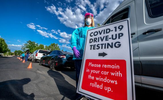 """Sign of a COVID-19 test center with the text """"COVID-19 drive up testing"""" and instructions to remain in cars with windows rolled up"""""""