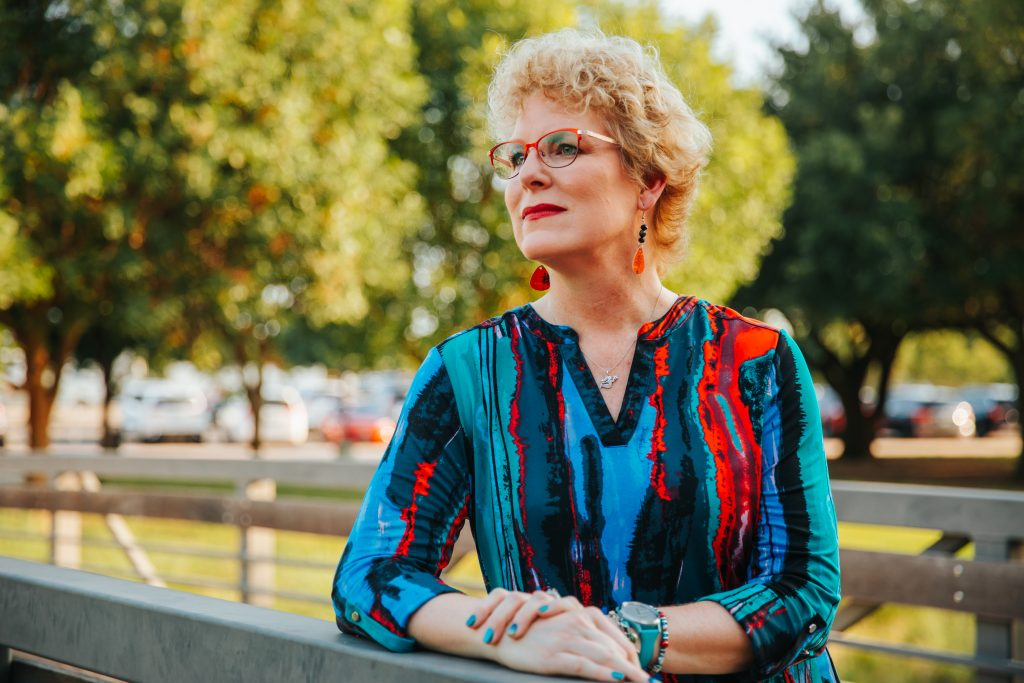 Erika Burkhardt photographed wearing a red, blue, black and green blouse