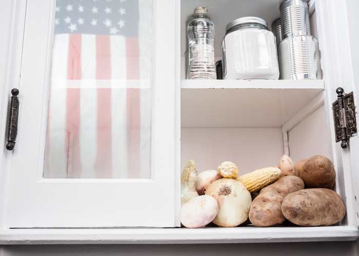 A cabinet other with potatoes, corn, and onions on one shelf and jars on the top shelf