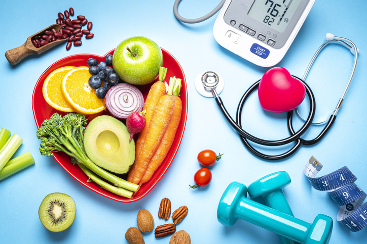 Vegetables and fruit in a red heart shaped bowl. Next to it is assorted healthy foods, dumbbells, a stethoscope and more