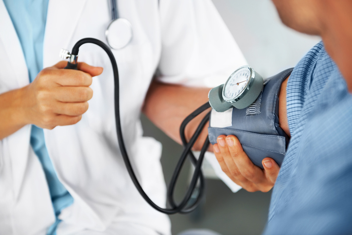 A medical professional checks a patient's blood pressure