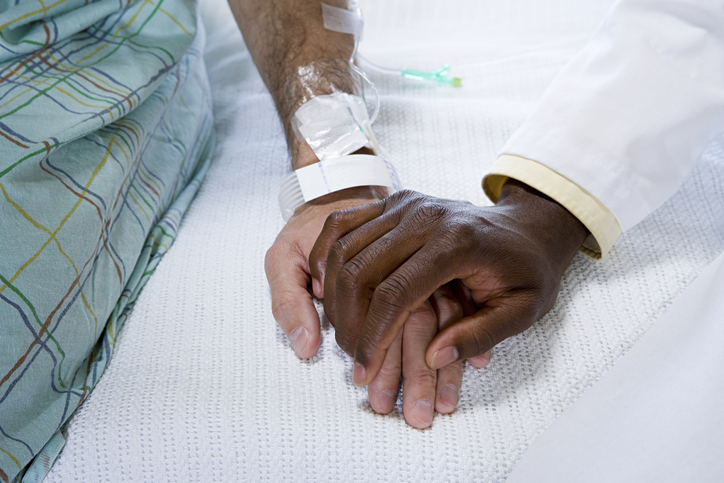 Two hands holding, likely a hospital patient in a gown and a doctor in a white coat