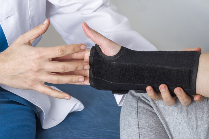 Medical professional assisting someone with a wrist cast