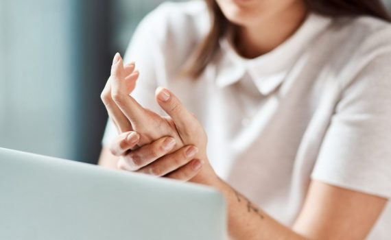 Woman holding wrist, used to explain carpal tunnel syndrome